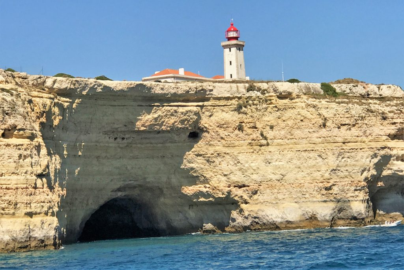 Ausflugsboote lieben Grottenfahrten mit Touristen an der Algarve, etwa in Alfanzina mit seinem Leuchtturm